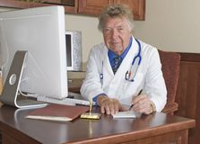 Doctor 12. Elderly doctor sitting at his desk writing Royalty Free Stock Photography