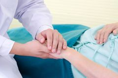 Friendly doctor holds the woman patient`s hand to encourage and trust medical treatment with heart at the hospital. Patient cheerful and expert take care royalty free stock photo