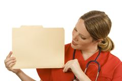 Doctor. Female doctor in orange scrubs holding a blank file folder Royalty Free Stock Photos