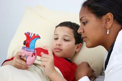 Doctor. Child laying sick in bed at the hospital with doctor Stock Photo