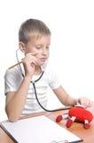 Doctor 7 años del muchacho aislado en blanco Fotografía de archivo libre de regalías