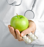 Doctor. Green apple and a pills is in the hands of doctor Royalty Free Stock Photos