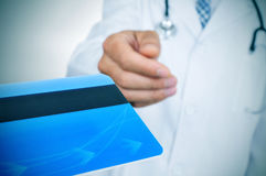 Doctor accepting a credit card Royalty Free Stock Photos
