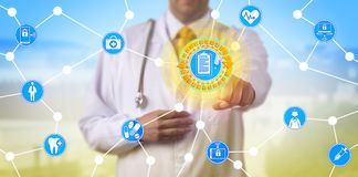 Doctor Accessing Data Via Internet Of Things. Unrecognizable doctor accessing electronic health records in network of interconnected physical devices. Healthcare royalty free stock photography