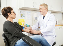 Doctor Adjusting Band Before Blood Test. Smiling male doctor adjusting band before blood test in hospital royalty free stock photography