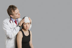 Doctor adjusting bandage on patient's head Royalty Free Stock Photo