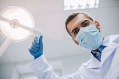 Doctor adjusting lamp in modern dental clinic royalty free stock photography