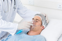 Doctor adjusting oxygen mask on patient Royalty Free Stock Photos