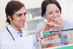 Doctor adjusting scale for excited patient Royalty Free Stock Photo