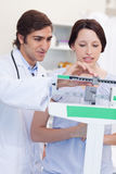 Doctor adjusting scale for his patient Stock Photography
