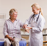 Doctor adjusting senior woman wrist splint Royalty Free Stock Photo