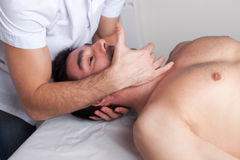 Doctor adjusting the spinal column. Of a middle aged man Royalty Free Stock Image