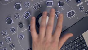 Doctor adjusts the X-ray medical equipment using its the control panel. 4K stock footage