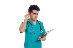 Doctor adulto joven en uniforme del azul con el estetoscopio en su cuello aislado en el fondo blanco Imagen de archivo