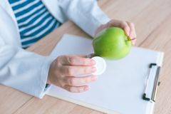 Doctor advising apple instead of pills and antibiotics. Female hand in white coat holding green fruit as favorable way to achieve and maintain healthy royalty free stock photos