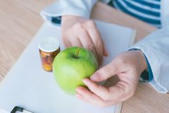 Doctor advising apple instead of pills and antibiotics. Female hands in white coat with green fruit as favorable way to achieve and maintain healthy lifestyle royalty free stock photo