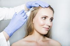 Doctor aesthetician makes head beauty injections to female patient on white background. Doctor aesthetician with blue medical gloves and white medical gown makes Stock Images