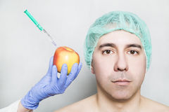 Doctor aesthetician makes beauty injections to apple near male patient Stock Photos