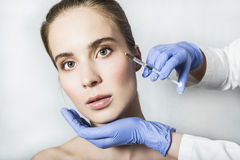 Doctor aesthetician makes face beauty injections to female patient Royalty Free Stock Photos