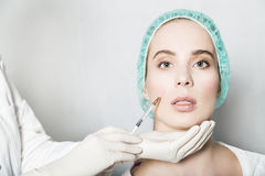 Doctor aesthetician makes face beauty injections to female patient. Doctor aesthetician makes hyaluronic acid beauty injections in the nasolabial fold of female Stock Image
