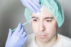 Doctor aesthetician makes face beauty injections to male patient Royalty Free Stock Images