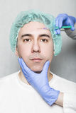 Doctor aesthetician makes face beauty injections to male patient Royalty Free Stock Photo