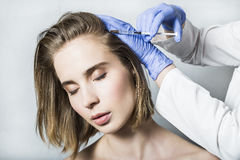 Doctor aesthetician makes head beauty injections to beautiful female patient. Doctor aesthetician in blue medical gloves makes hyaluronic acid rejuvenation Royalty Free Stock Images