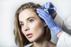 Doctor aesthetician makes head beauty injections to beautiful female patient Stock Images