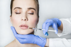Doctor aesthetician makes lips correction and augmentation to female patient Stock Photography