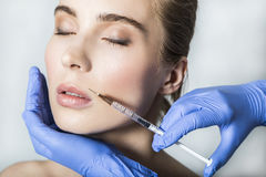 Doctor aesthetician makes lips correction and augmentation to female patient Royalty Free Stock Photos