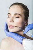 Doctor aesthetician makes lips correction and augmentation to female patient Stock Photo