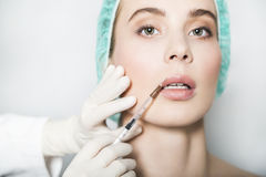 Doctor aesthetician makes lips correction and augmentation to female patient Stock Images