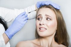 Doctor aesthetician trying to make head beauty injections to female patient Royalty Free Stock Photo