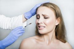 Doctor aesthetician trying to make head beauty injections to female patient Royalty Free Stock Photography