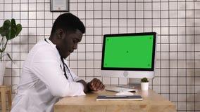 Doctor africano aburrido que espera algo por la pantalla de ordenador Visualización blanca almacen de metraje de vídeo