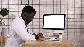 Doctor africano aburrido que espera algo por la pantalla de ordenador Visualización blanca almacen de video