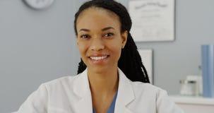 Doctor africano de la mujer que se sienta en la sonrisa del escritorio Imagenes de archivo