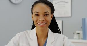 Doctor africano de la mujer que se sienta en la sonrisa del escritorio Imágenes de archivo libres de regalías
