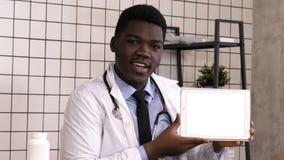 Doctor africano serio hermoso que presenta el producto en la pantalla de la tableta Visualización blanca almacen de video
