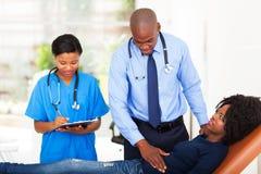 Doctor africano que examina Imagenes de archivo