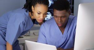 Doctor afroamericano de la mujer que señala en la información sobre el ordenador imagenes de archivo