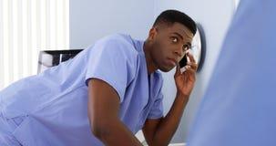 Doctor afroamericano en hablar móvil con el colega y usar el ordenador Foto de archivo libre de regalías