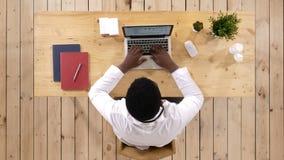 Doctor afroamericano joven en el trabajo, con el ordenador portátil almacen de video
