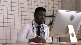Doctor afroamericano joven que hace notas y que mira para arriba algo en su ordenador foto de archivo libre de regalías