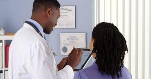 Doctor afroamericano que toma historia paciente con la tableta fotos de archivo