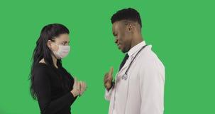 Doctor afroamericano sonriente que habla con el paciente femenino metrajes