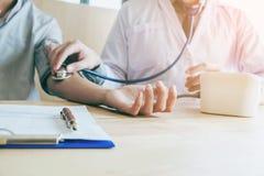Doctor al paciente arterial de la mujer de la presión arterial de Measuring en la derecha imagenes de archivo