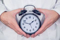 Doctor with alarm clock. In hands, it is time to make an appointment for your next medical exam Stock Photos
