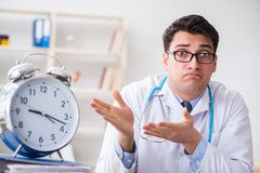 The doctor with alarm clock in urgent check-up concept. Doctor with alarm clock in urgent check-up concept Royalty Free Stock Image