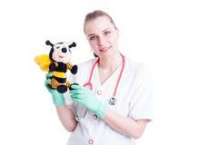 Doctor alegre de la mujer que sostiene un juguete de la felpa de la abeja Foto de archivo libre de regalías